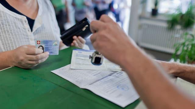 Zollbeamter stempelt einen Ausfuhrschein für eine Schweizerin.