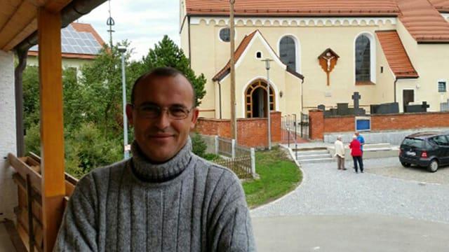 Hassan Hammed lächelnd vor einer Kirche.