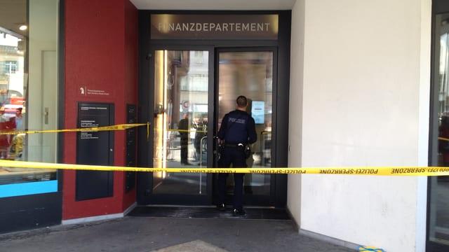 Polizist vor Haupteingang der Basler Finanzverwaltung, mit Absprerrbändern