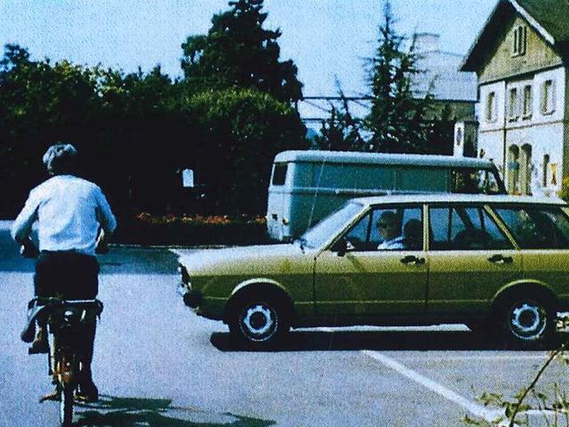 Ein Fahrradfahrer fährt an einem alten VW vorbei.