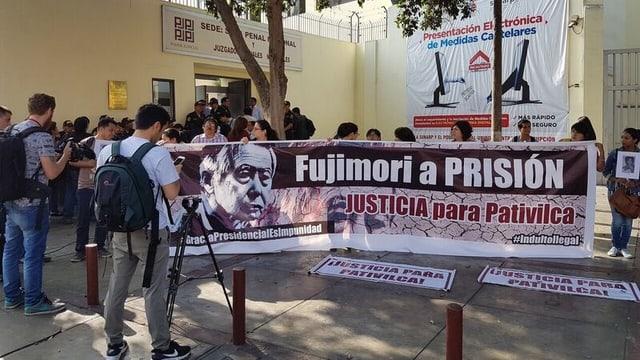 Angehörigen der Toten protestieren mit einem Transparent Fujimori a Prision.
