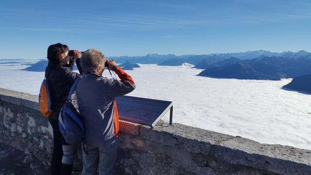 Zwei Frauen geniessen mit Feldstechern die Aussicht über dem Nebelmeer.