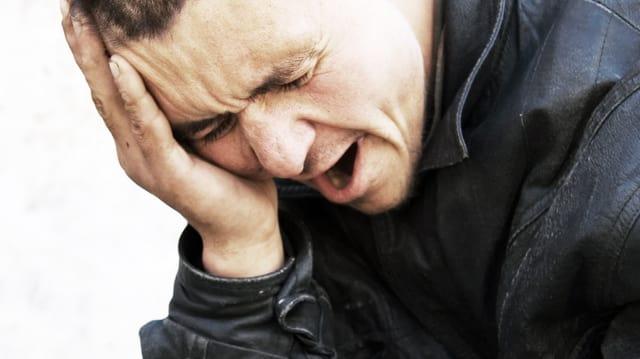 Mann stützt seinen Kopf auf die Hand und versucht verzweifelt, zu Atem zu kommen.