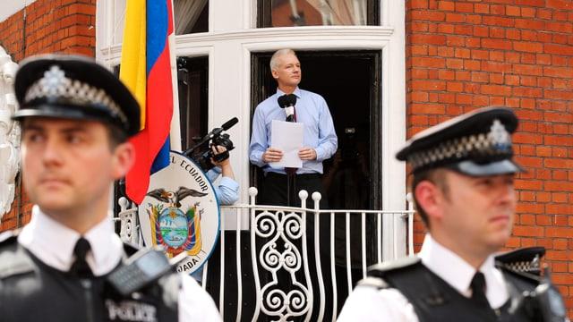 Assange spricht von Balkon aus zu Medien, davor britische Polizisten