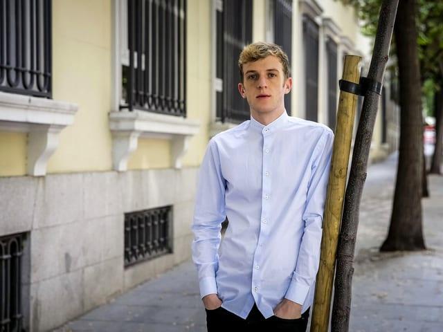 Édouard Louis steht an einen Baum gelehnt, trägt ein weisses Hemd.