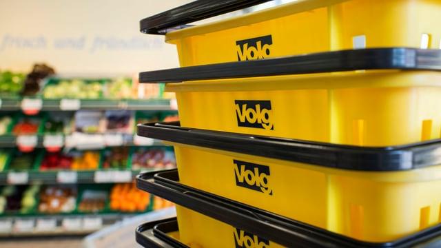 Blick in einen Volg-Laden: Im Vordergrund Einkaufskörbe mit Logo, im Hintergrund Warenauslagen.