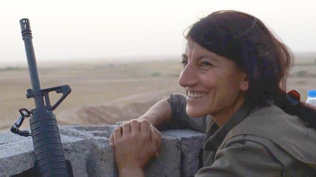 Kämpferinnen lacht, neben ihr ein Gewehr.