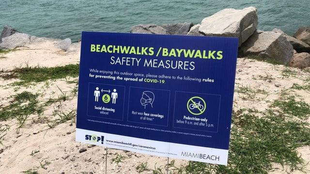 Plakat mit den Corona-Vorschriften am Strand.