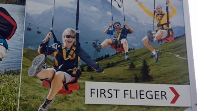 Drei Touristen rasen lachend an einem Seil talwärts.