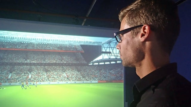 Urs Schnyder schaut sich auf einem Bildschirm Abseitsszenen eines Fussballspiels an.