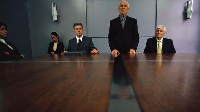 Einige Leute an einem Konferenztisch, einer steht.