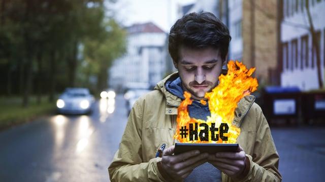 Ein junger Mann schaut traurig auf ein Tablet, aus dem Flammen züngeln und der Hashtag #hate.
