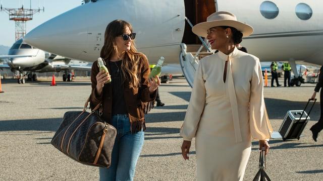 Maggie bietet Grace zwei Getränke an, als sie ihre Chefin am Flughafen abholt.