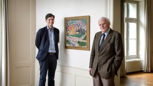 Ein Mann steht neben einem Gemälde.