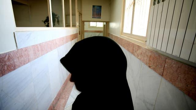 Eine Frau mit Kopftuch steht in einem Gang