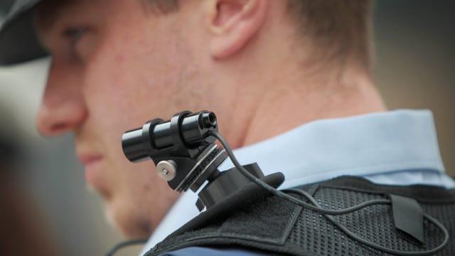 Ein Polizeibeamter mit einer Bodycam auf der Schulter.