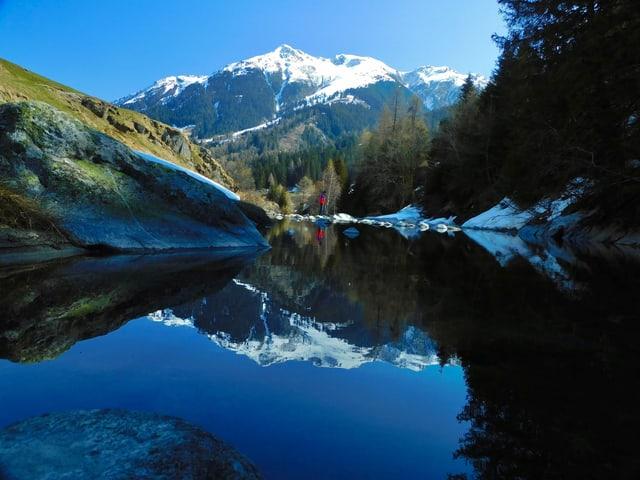 Die Schneeberge spiegeln sich im glatten Wasser.