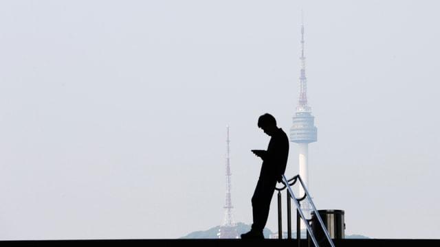 Ein Mann schaut auf sein Smartphone, im Hintergrund sieht man den Seoul Tower.
