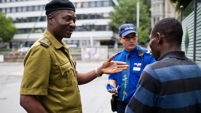 Polizisten aus Nigeria und der Schweiz kontrollieren einen nigerianischen Mann.