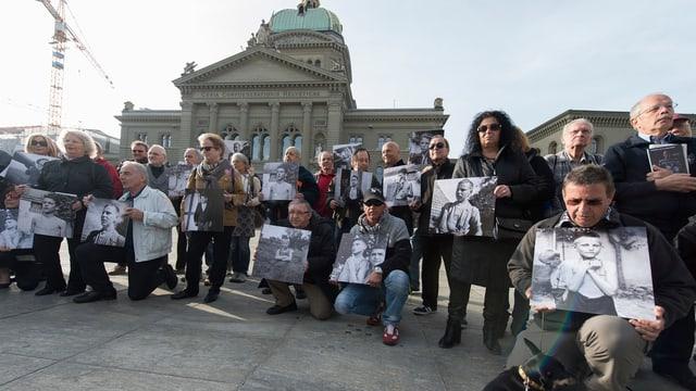 Ehemalige Verdingkinder und Opfer von fürsorgerischen Massnahmen posieren mit Kinderfotos vor dem Bundeshaus am 31.3.2014