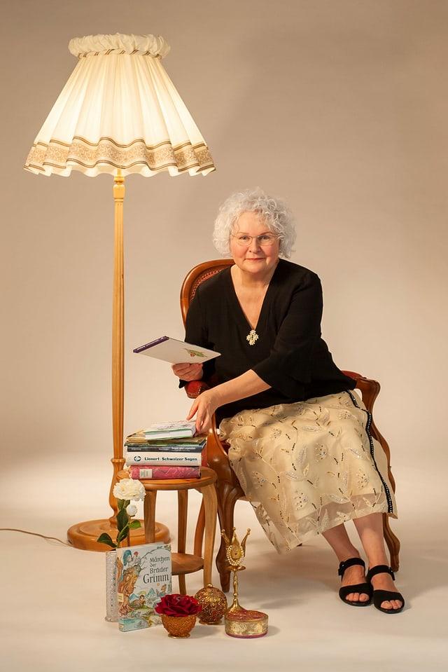 Frau sitzt auf Stuhl. Daneben ein Tisch auf dem Märchenbücher gestapelt sind.