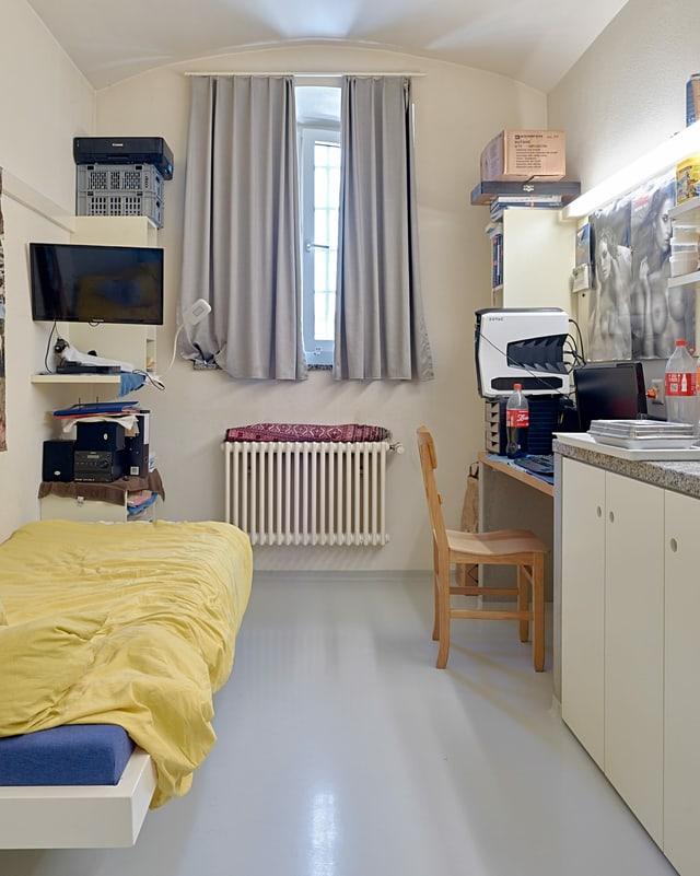 Eine Gefängniszelle: ein Bett, ein Schreibtisch, ein TV und ein Fenster.