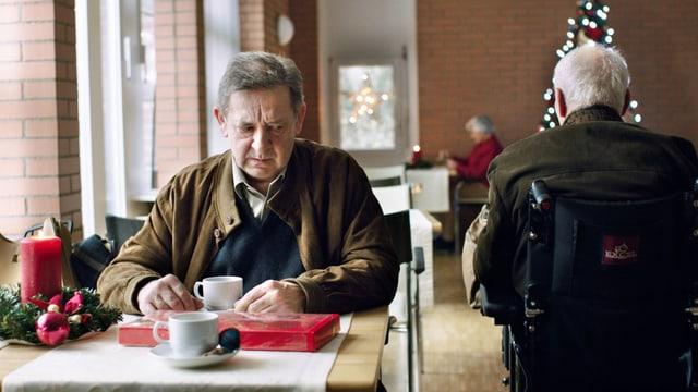 Ein einsamer Mann an einem Tisch im Altersheim, ein anderer fährt im Rollstuhl an ihm vorbei
