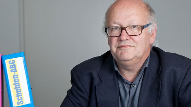 Ein Mann mit Brille, daneben ein Ordner mit der Aufschrift Schulden-ABC.