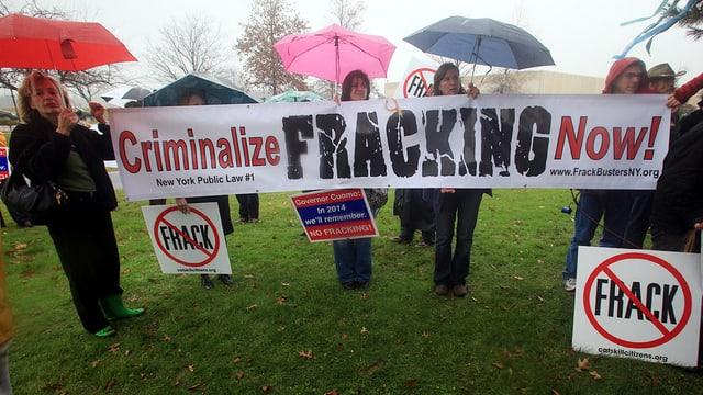 """Demonstranten mit Regenschirmen und Plakat """"Criminalize Fracking now"""""""