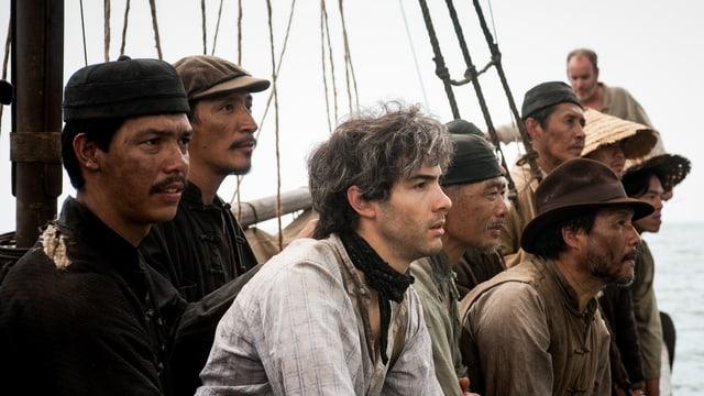Männer auf einem Schiff blicken alle in eine Richtung.
