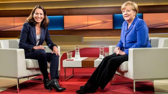 Anne Will (links) und Angela Merkel sitzen auf dem Set der Talkshow.