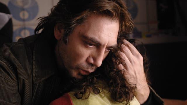 Ein Mann hält ein Kind in seinen Armen.