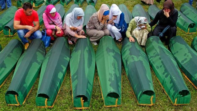 Frauen vor Särgen.