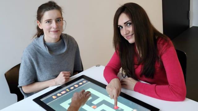 Zwei Frauen sitzen am Tisch und schauen in die Kamera.