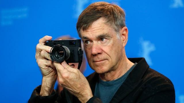 Nahaufnahme des Berlinale-Stammgasts Gus Van Sant mit einer Fotokamera in der Hand.