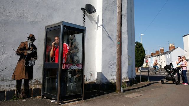 Ein Mann telefoniert in einer Telefonzelle. Auf einem Graffiti hinter ihm ist ein Mann auf eine Mauer gesprüht, die ihn abhört.