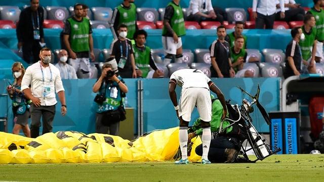 Der Greenpeace-Aktivist war nach seinem missglückten Flug selber bei der Landung gestrauchelt. Der deutsche Spieler Antonio Rüdiger stand ihm am nächsten und eilte zu ihm.
