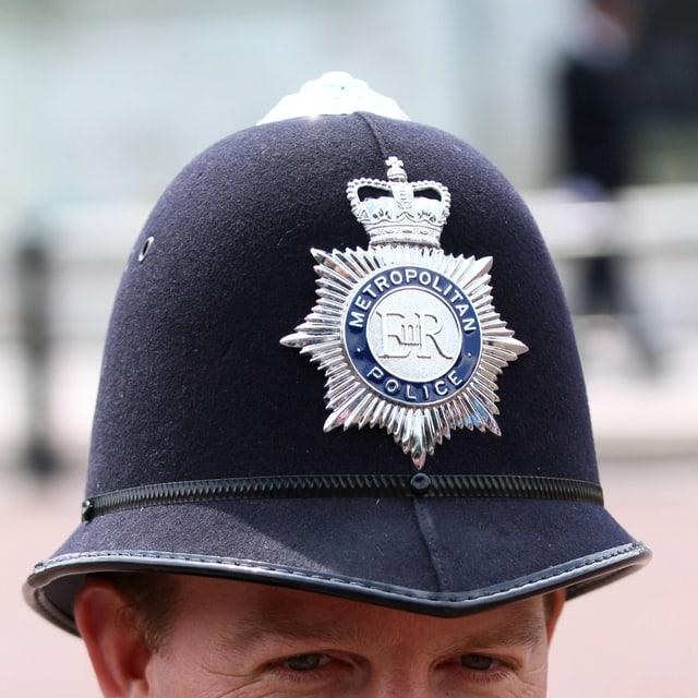 """Blick auf einen Helm aus Filz, vorne ein silbernes Kennzeichen mit der Aufschrift """"Metropolitan Police""""."""