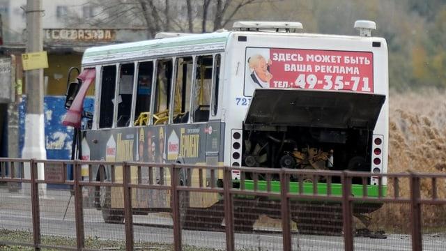 Ein Bus mit geborstenen Scheiben und offenen Türen steht am Strassenrand.