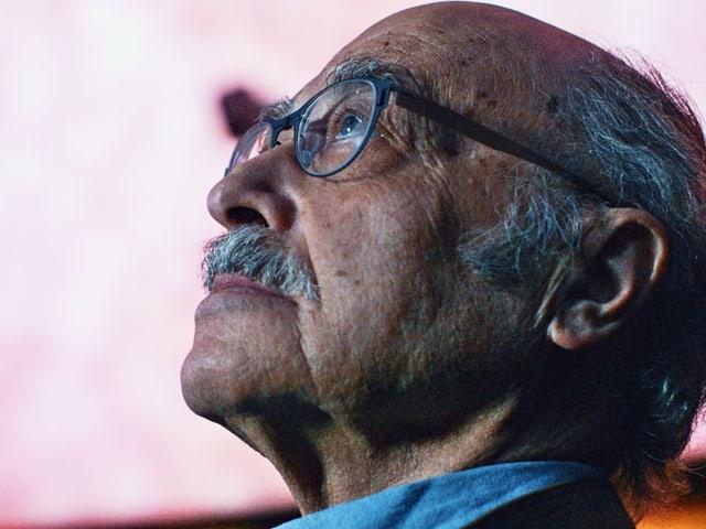 Ein Mann mit Brille schaut in die Höhe.