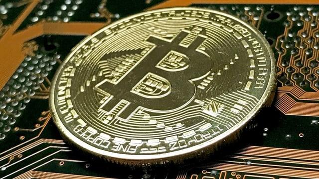 Eine Münze stellt die digitale Währung «Bitcoin» dar.