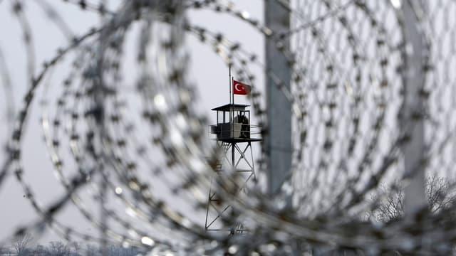 Ein Drahtzaun, im Hintergrund ein Turm mit türkischer Flagge