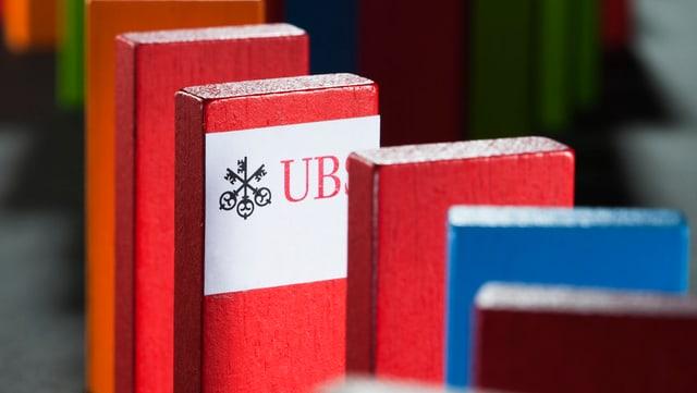 Farbige Holzklötzchen, aufgereiht wie beim Domino, auf dem mittleren prangert das UBS-Logo.