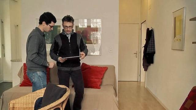 Ein Mann zeigt einem anderen Mann den Bildschirm seines Tablets, sie stehen in einer Wohnung.