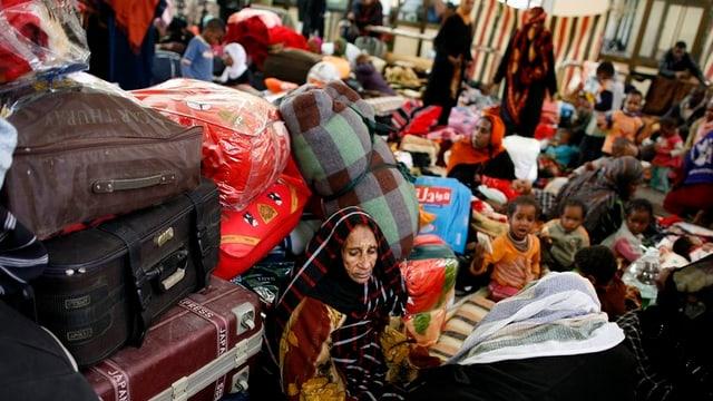 Flüchtlinge, darunter Kinder warten neben Stapeln von Koffern und Taschen.