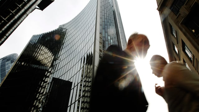 Symbolbild: Zwischen den Hochhaustürmen der Canary Wharf in London gehen Menschen vorbei.