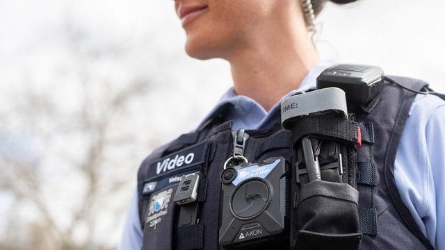 Eine Polizistin trägt eine Kamera auf der Brust.