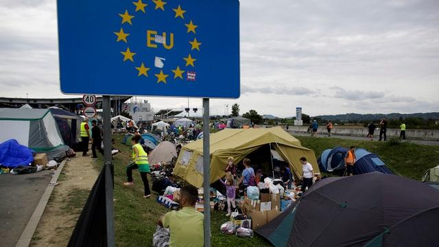 EU-Flagge vor einem Zeltlager mit Flüchtlingen
