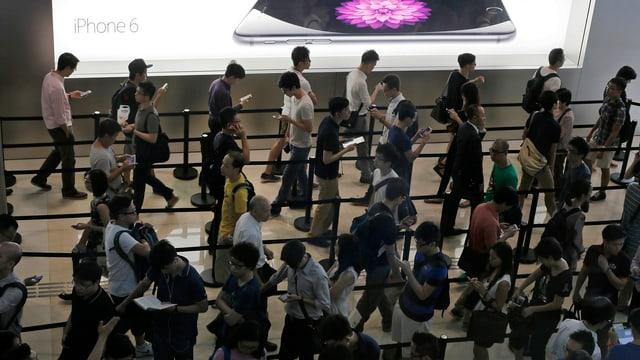 Menschen mit Tablets und Smartphones in einer Warteschlange.