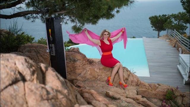 Beatrice Egli sitzt auf einem Felsen am Meer und streckt die Arme in die Höhe.